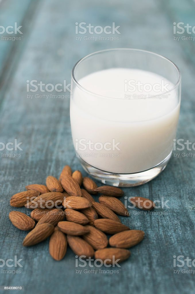 Glass Of Almond Milk On Blue Wooden Background With Almond Nuts stock photo