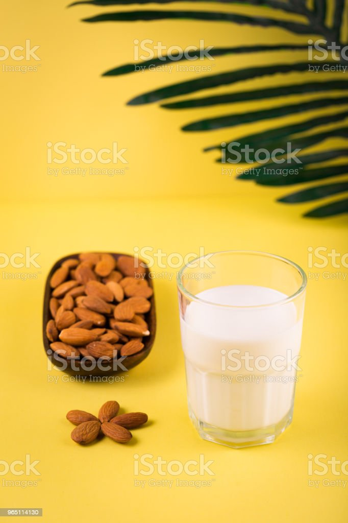 Glass of almond milk on yellow tropic summer background zbiór zdjęć royalty-free