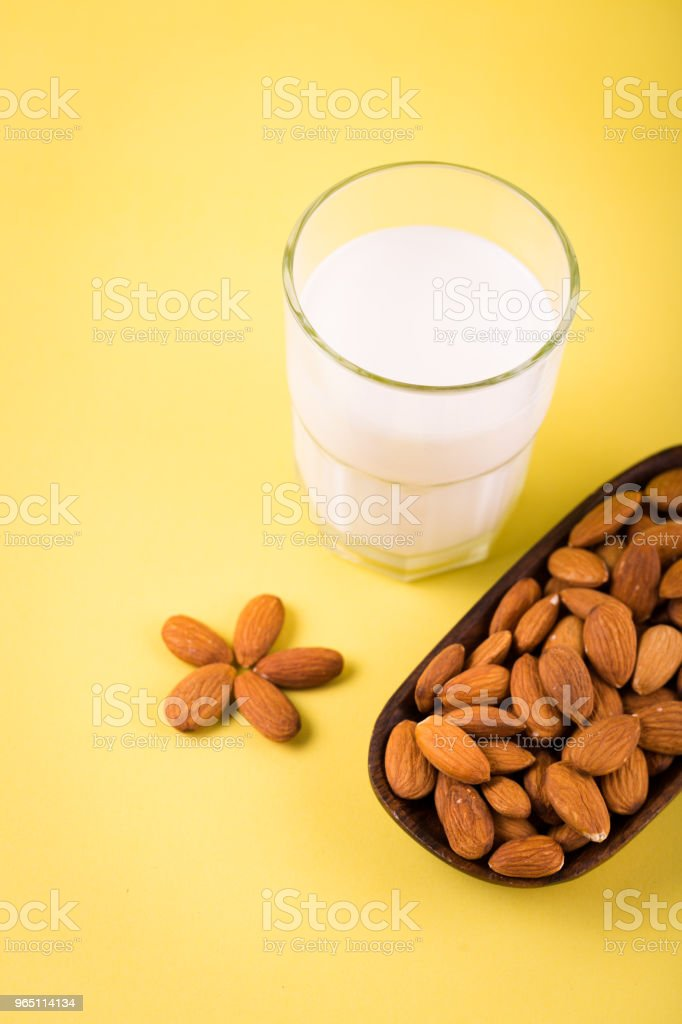 Glass of almond milk on yellow tropic summer background royalty-free stock photo