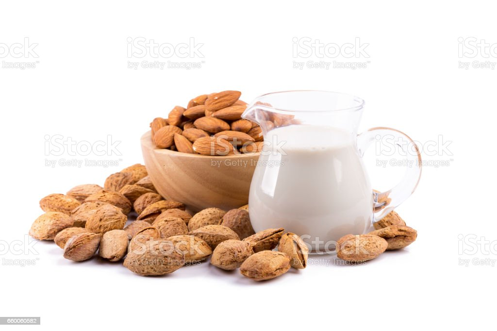 Glass of Almond milk with a heap of almonds on white background stock photo