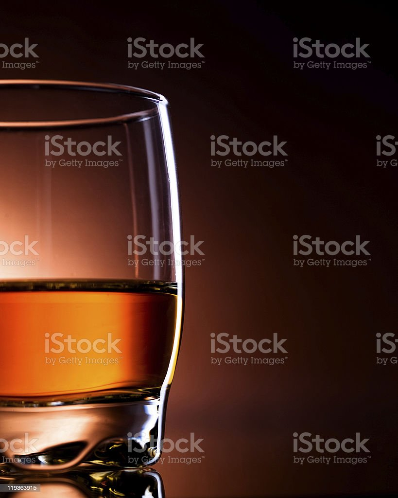 Glass of amber liquid on black background  royalty-free stock photo