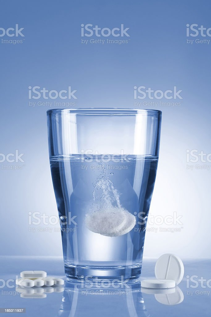 Glass of analgesic tablets stock photo