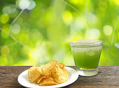 glass of apple juice and potato chips over abstract green background