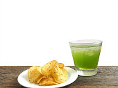 glass of apple juice and potato chips isolated on white background