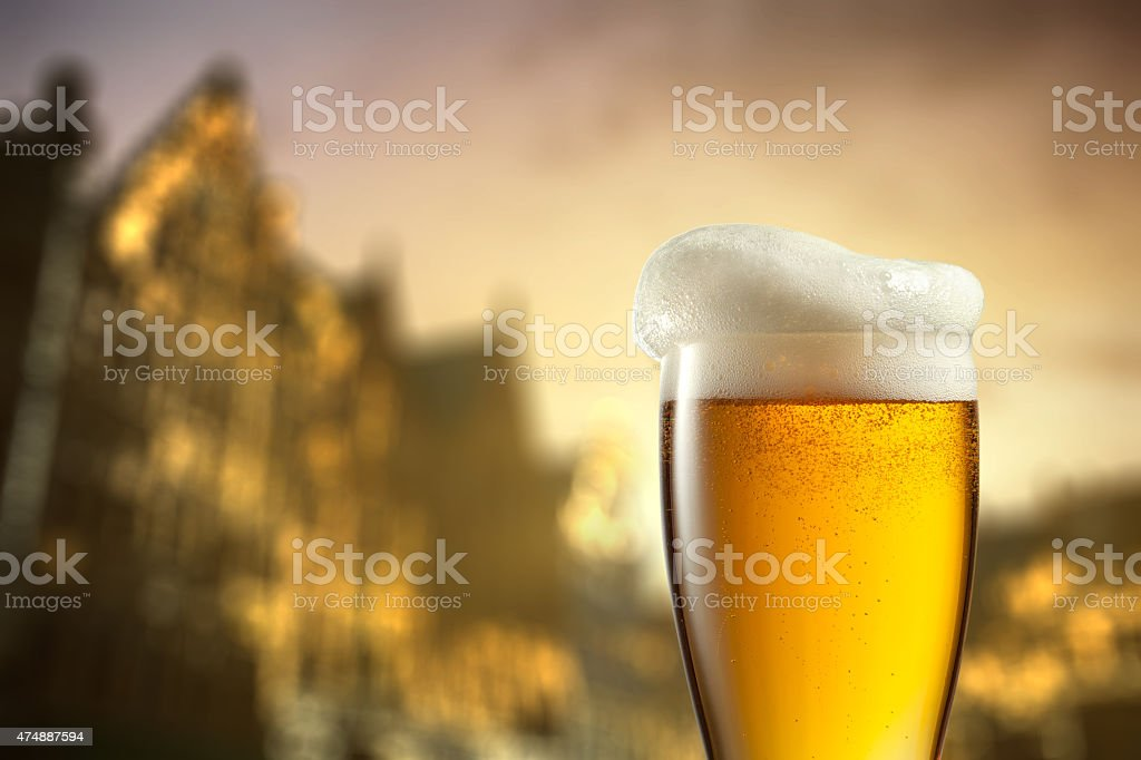 Glass of beer against blurred european city stock photo