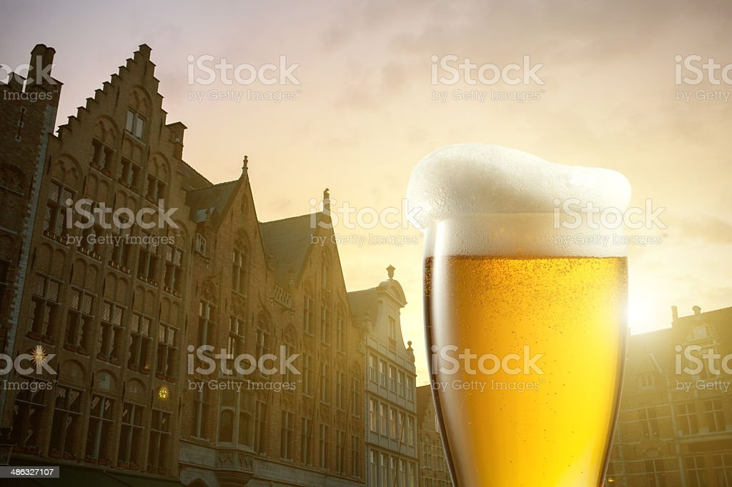 Glass of beer against silhouettes of houses in Bruges, Belgium stock photo