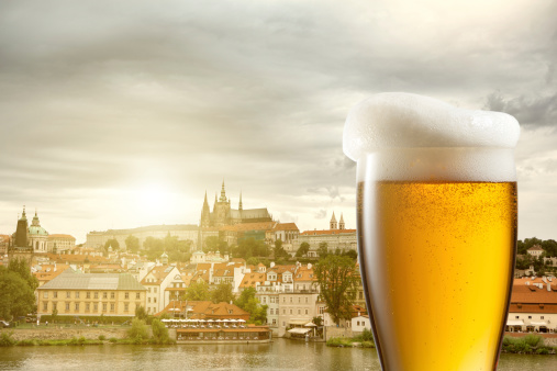 Glass of beer against view of Prague