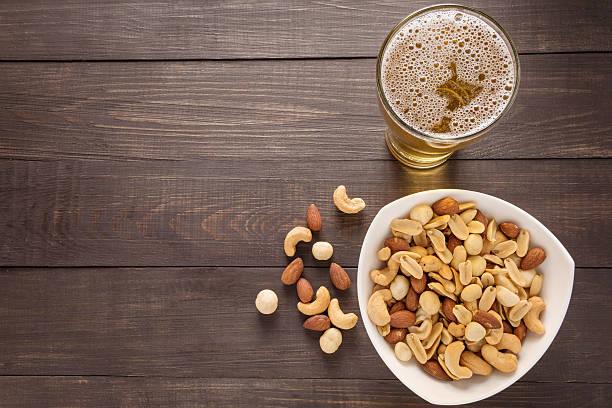 Bicchiere di birra e mandorle, macadamia, arachidi, anacardi e - foto stock