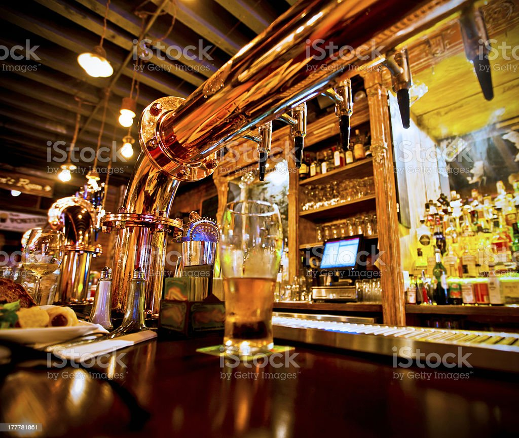 Glass of beer and beer taps in a bar stock photo