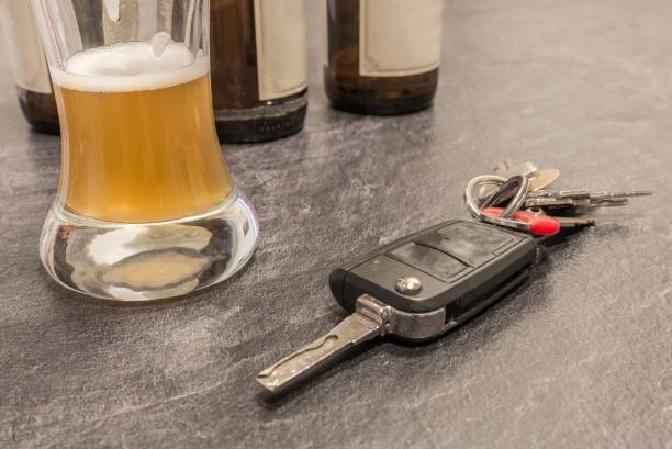 Glass of Beer and car key on grey table stock photo