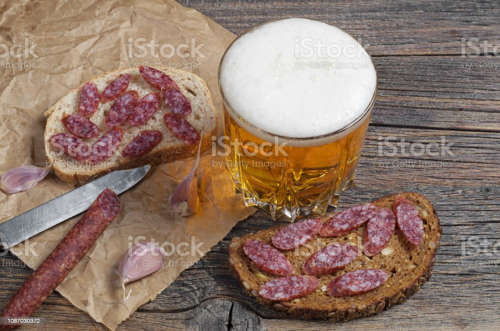 Glass of beer and sandwiches with sausage stock photo