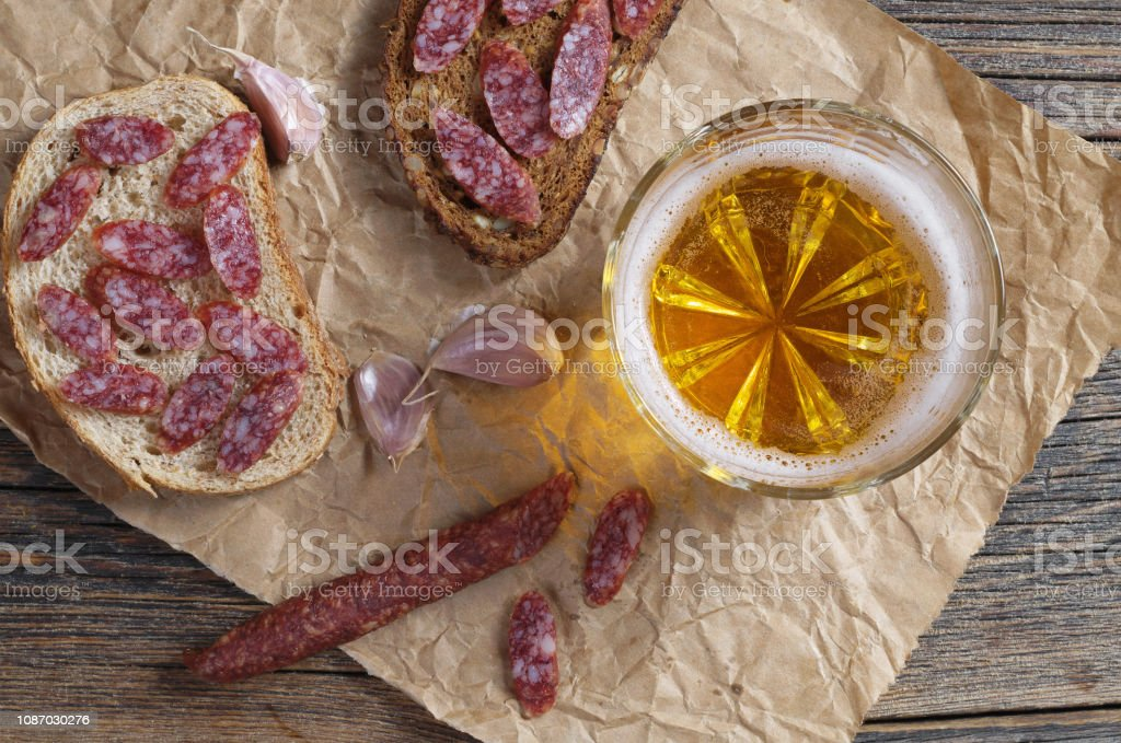 Glass of beer and sandwiches with smoked sausage stock photo