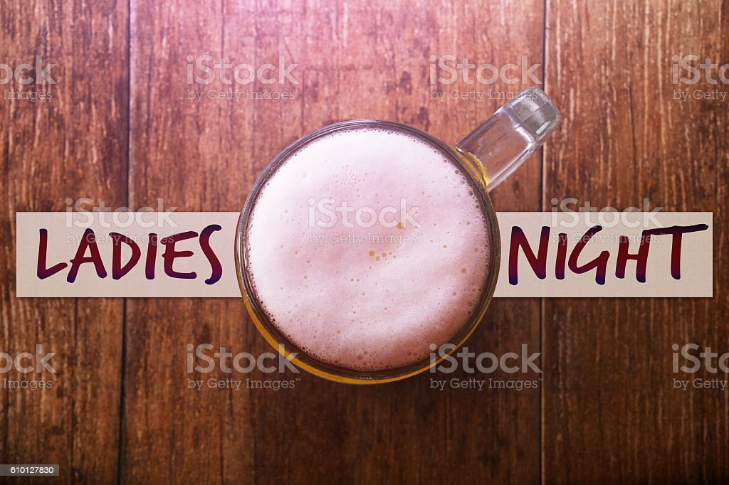 Glass of Beer at Bar with Note : Ladies Night stock photo