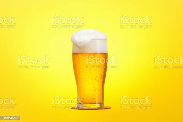 Glass of beer closeup with froth over yellow background picture id958236492?b=1&k=6&m=958236492&s=612x612&h=xdtof1q1kqk0qr2yv6xlln7yjs4it5b7b10ay5p3reg=