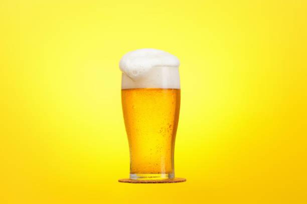 啤酒瓶特寫與泡沫在黃色背景 - 啤酒 個照片及圖片檔