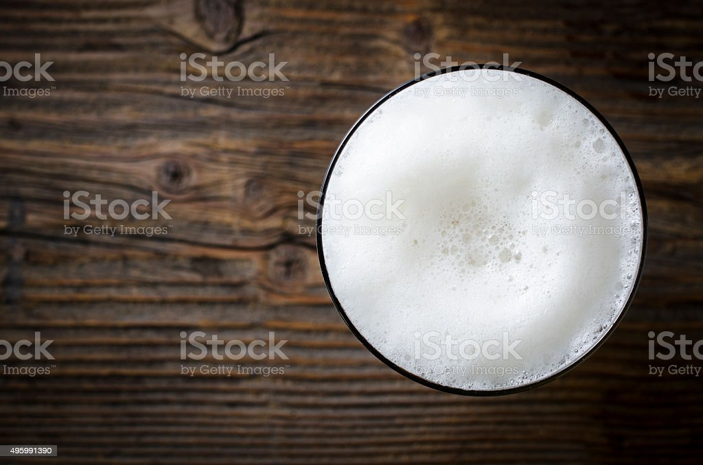 Glas Bier mit Schaum auf Holztisch – Foto