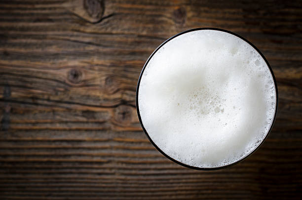 glass of beer foam over wooden table - beer foam stock photos and pictures