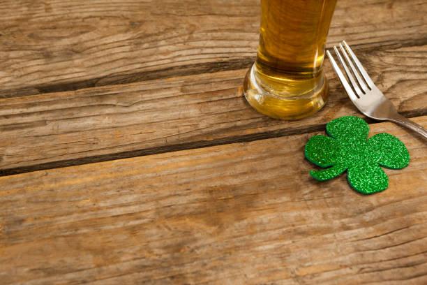 glas bier, gabel und shamrock für st. patricks day - st. patrick's day stock-fotos und bilder
