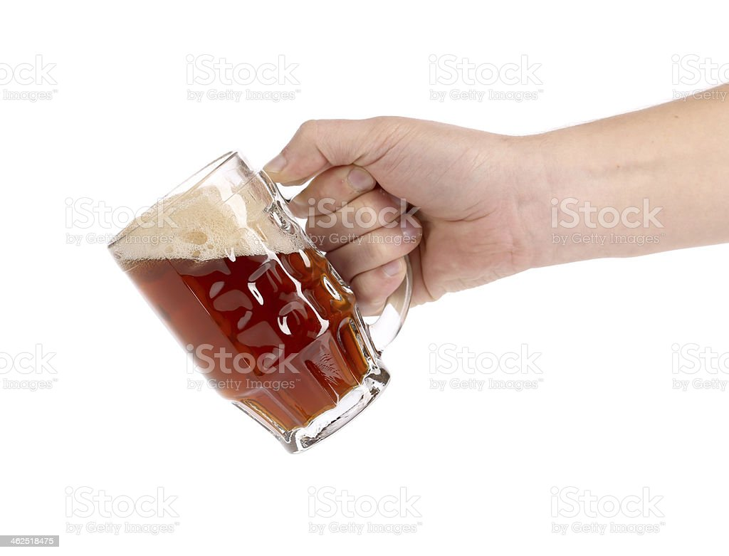 Glass of beer in hand. stock photo