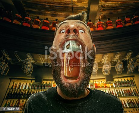 istock Glass of beer in man's mouth at bar 924939466