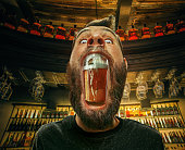 Glass of beer in man's mouth at bar