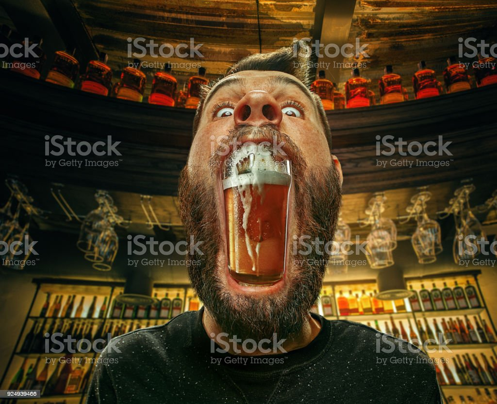 Glass of beer in man's mouth at bar stock photo