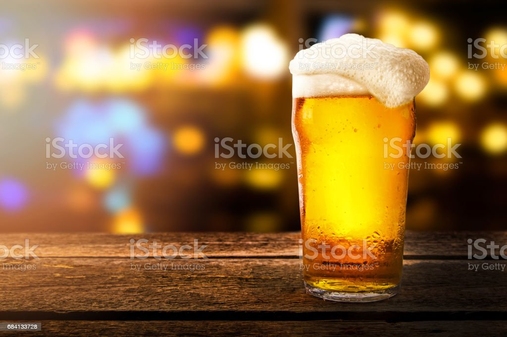 glass of beer on a table in a bar on blurred bokeh background stock photo