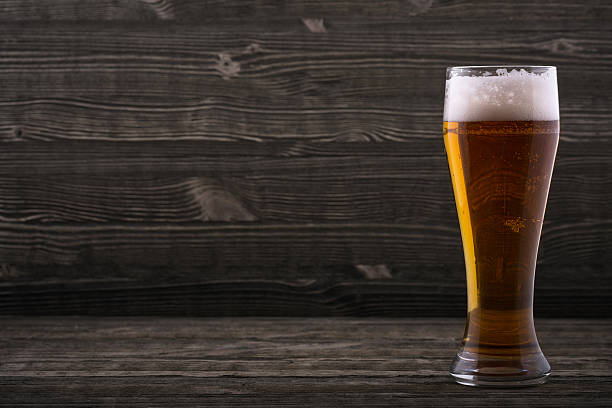 Glass of beer on a wooden countertop stock photo