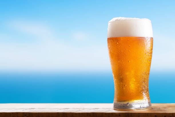 glass of beer on a wooden table on background of the sea stock photo