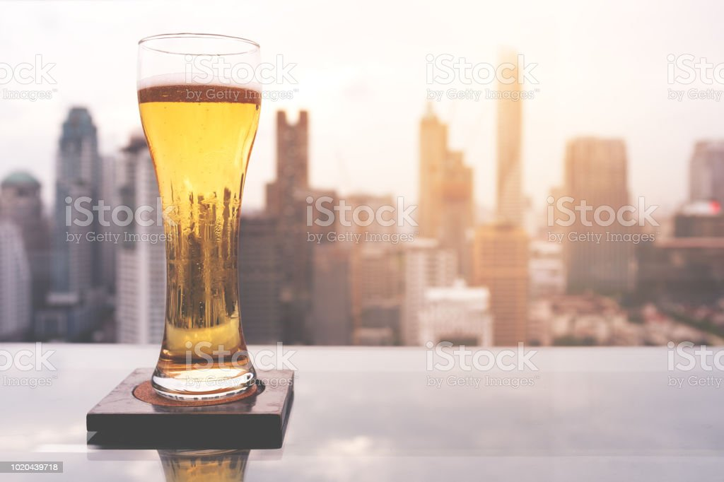 Glass of beer on table in rooftop bar in Bangkok - foto stock
