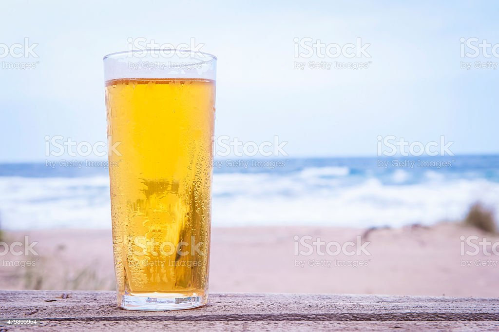 Glass of beer on the beach stock photo