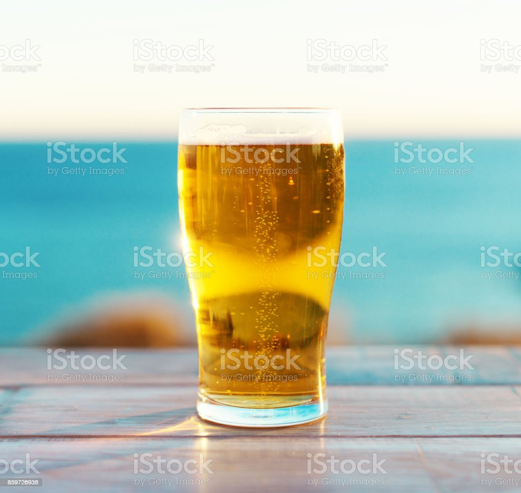Glass of beer on the sunset. stock photo