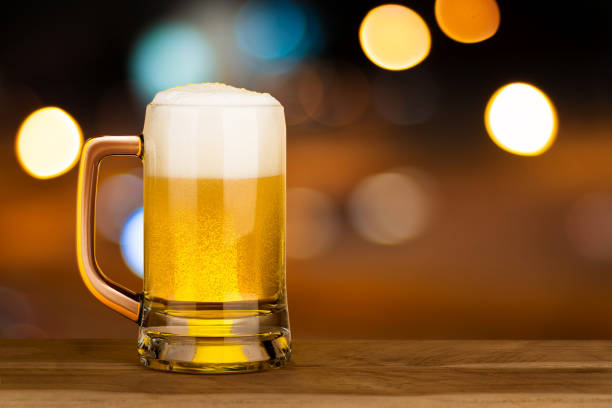 Glass of beer on wood table in pub with bokeh light night background , drinking alcohol celebration concept design with copy space Glass of beer on wood table in pub with bokeh light night background , drinking alcohol celebration concept design with copy space beer glass stock pictures, royalty-free photos & images