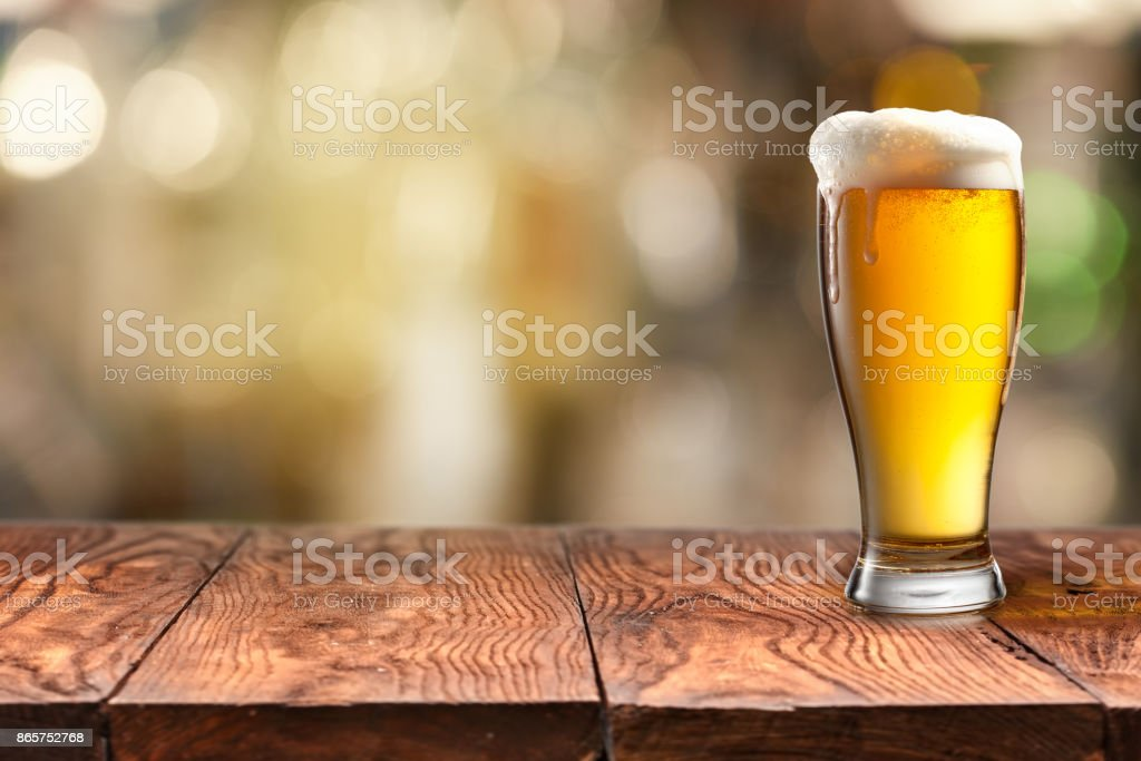 Glass of beer on wooden table and blurred background. stock photo