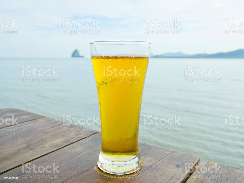 Glass of beer on wooden table at the restaurant stock photo