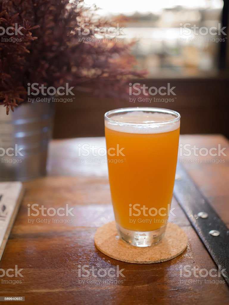 Glass of beer on wooden table in pub background stock photo