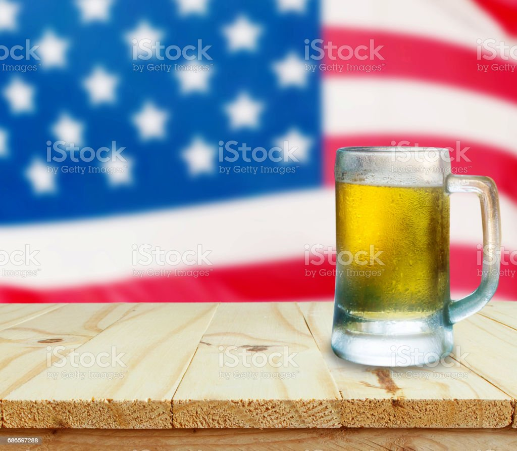 Glass of beer on wooden table. USA flag background royalty-free stock photo
