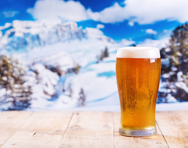 glass of beer over winter landscape glass of beer on wooden table over winter landscape apres ski stock pictures, royalty-free photos & images