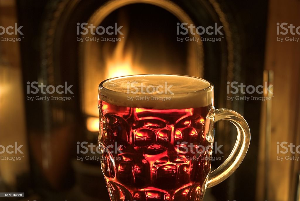 Glass of Beer Pint of beer by the fireside. Alcohol - Drink Stock Photo