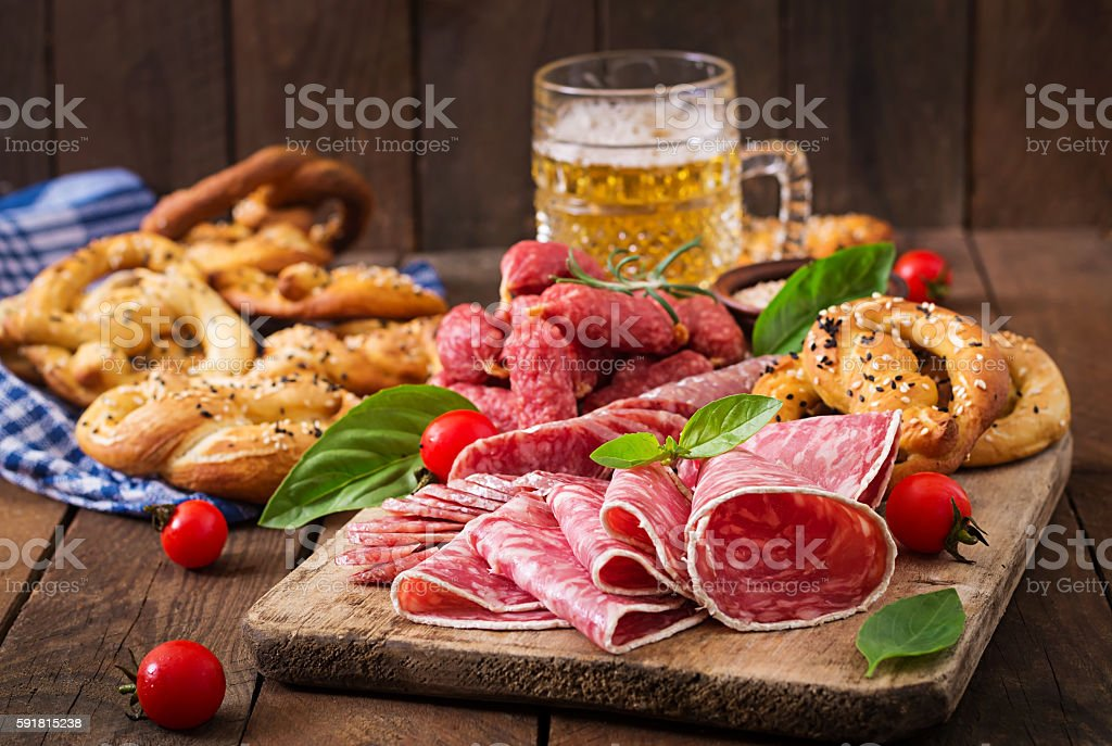 Glass of beer, pretzels and various sausages on wooden background. stock photo