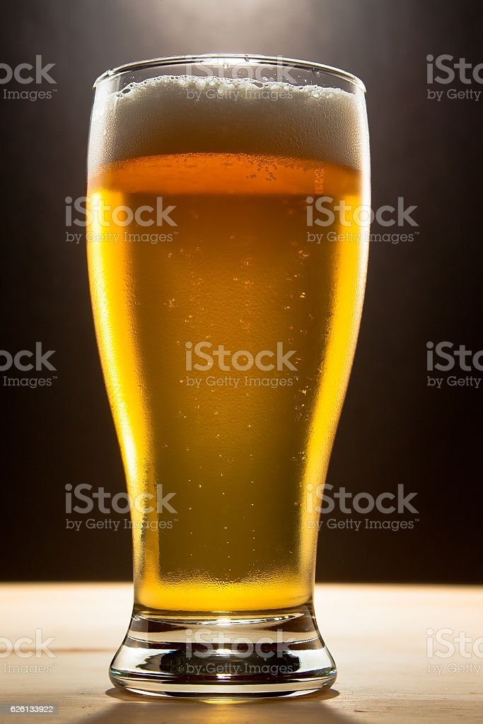 glass of beer shot against a black background stock photo