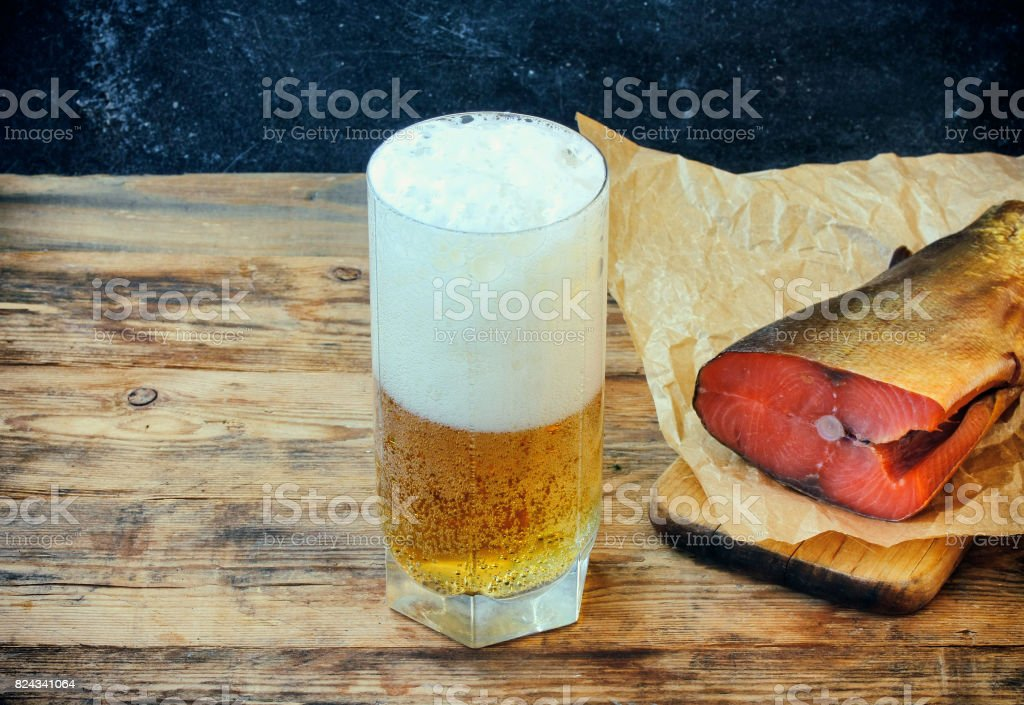 glass of beer with foam, smoked salmon on paper stock photo