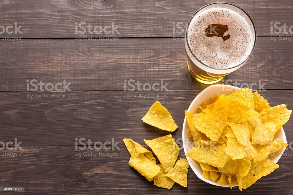 Glass of beer with nachos chips on a wooden background stock photo