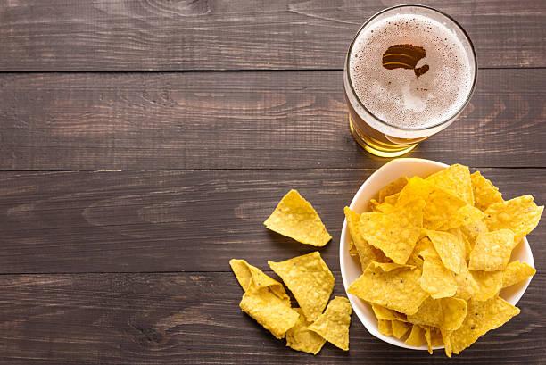 Bicchiere di birra con nachos chips su uno sfondo in legno - foto stock
