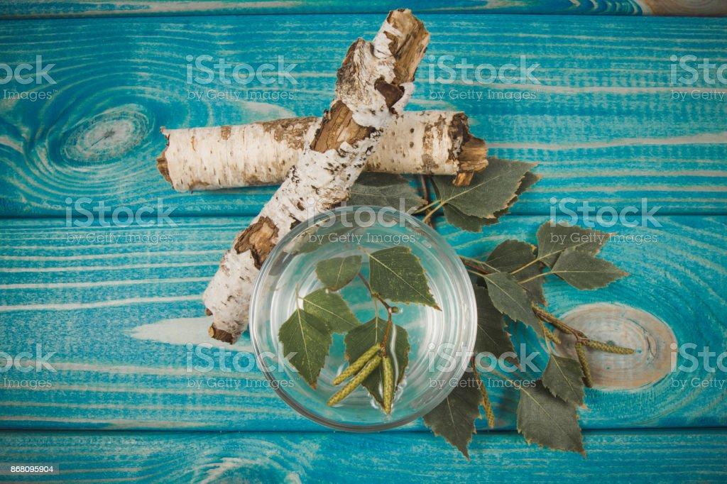 Een glas sap van de berk op houten achtergrond foto
