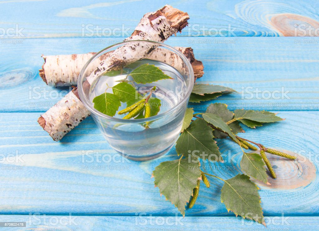 A glass of birch juice on wooden background stock photo
