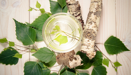 A glass of birch juice on wooden background