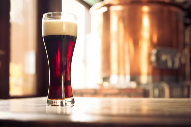glass of bitter ale beer in front of copper vat - dark beer stock photos and pictures