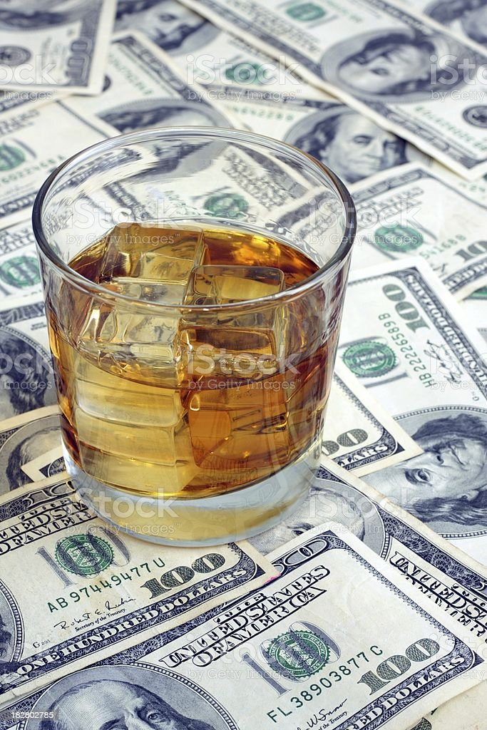 Glass of Bourbon on a Cash Background stock photo
