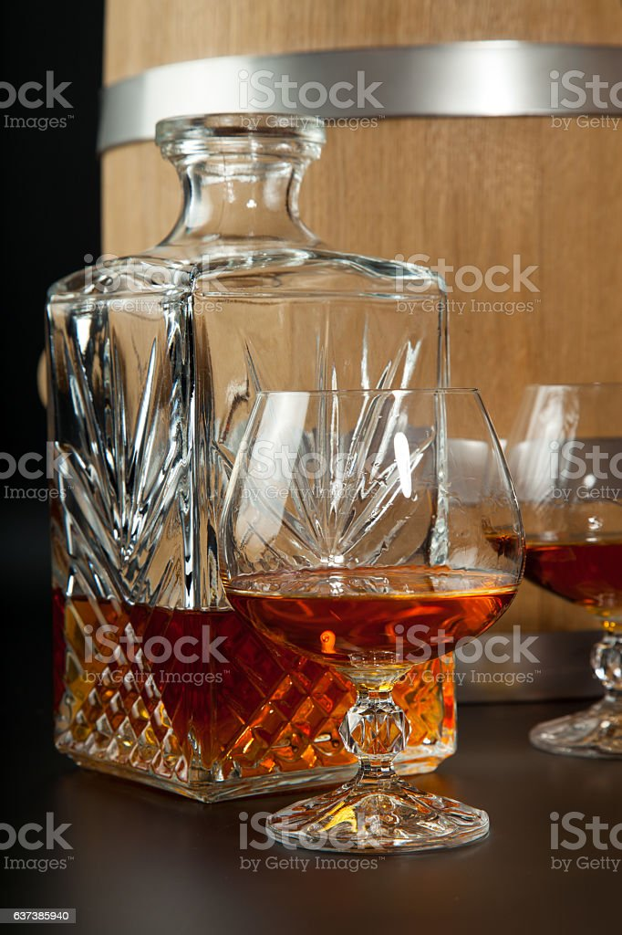Glass of brandy and a carafe on  background  oak barrels stock photo